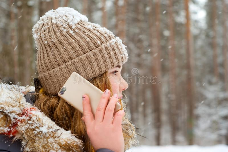 Girl talking on the phone in the winter park royalty free stock photography