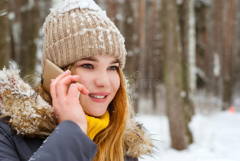 Girl talking on the phone in the winter park stock photos