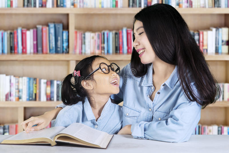 Girl talking with teacher in library royalty free stock photos