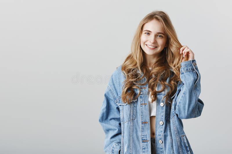 Girl talks casually with friend during walk. Indoor shot of happy attractive caucasian female model in denim jacket. Playing with hair strand while flirting or stock photos