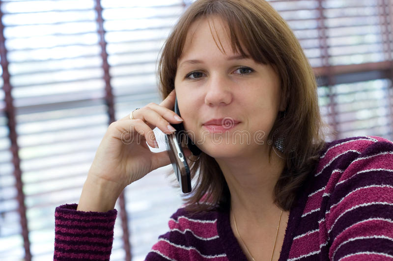 The girl talks by a mobile phone. At office stock photos