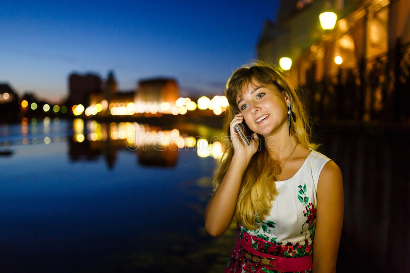 Girl talks on mobile phone. Pretty young girl talks on mobile phone in the night city royalty free stock images