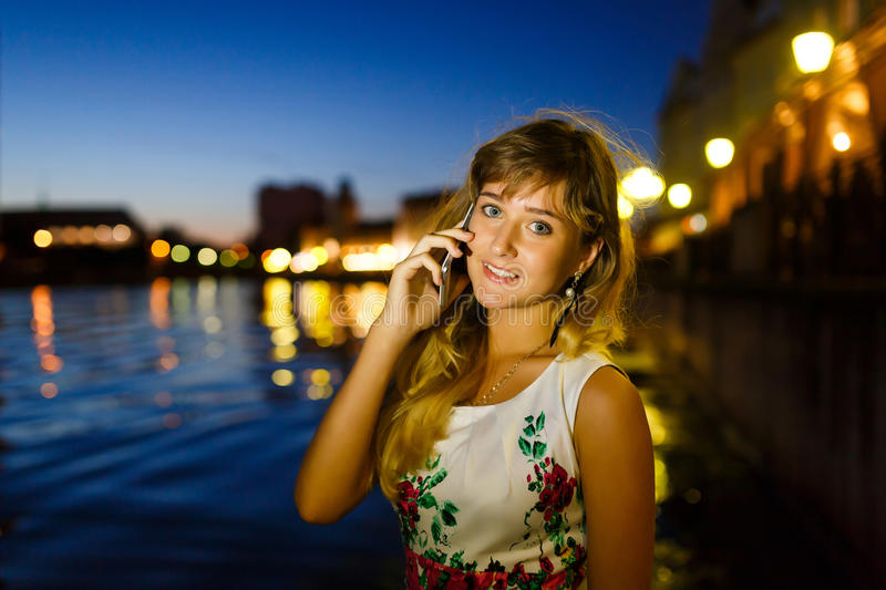 Girl talks on mobile phone. Pretty young girl talks on mobile phone in the night city royalty free stock photography