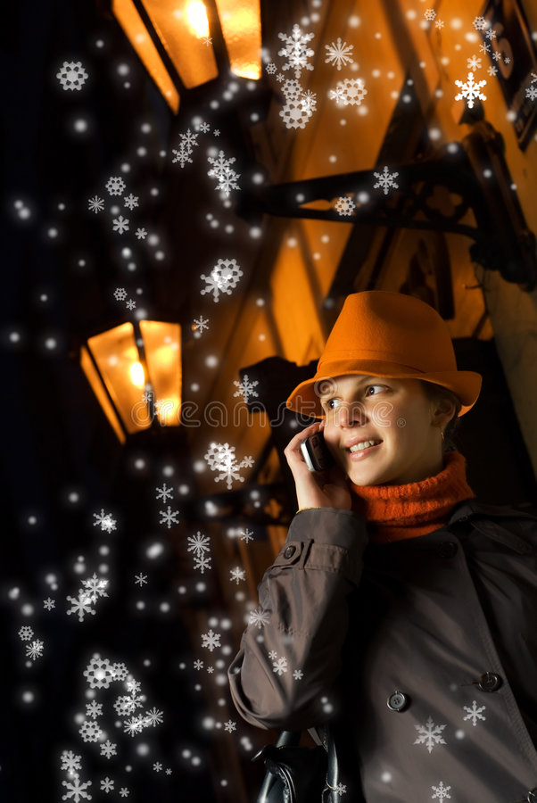 Girl talks on the phone. Beautiful girl talks on the phone at Christmas night royalty free stock photos
