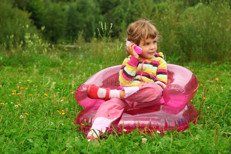 Download Girl Talks By Toy Phone In Inflatable Armchair Stock Photo - Image: 11411392