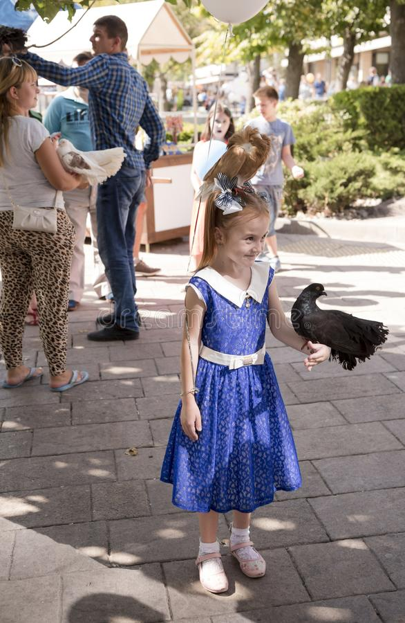 Girl with tame birds. Nearby there are participants of an attraction stock photo
