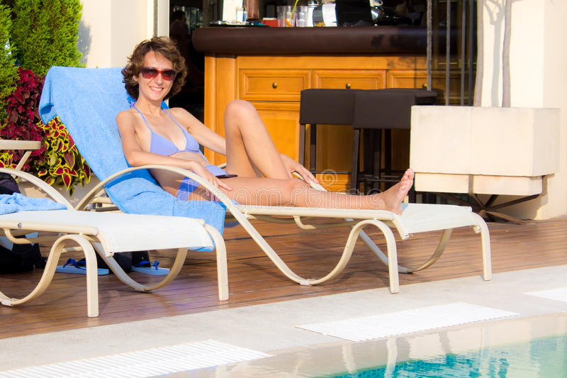 Girl tanning in summer. Girl in bikini tanning by the pool in summer royalty free stock photography