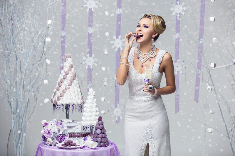Girl tasting cake. Beautiful young happy bride in felted gown eating wedding macaroon french style cake over snowy background and holding champagne glass stock photo