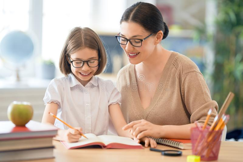 Girl with teacher in classroom stock image