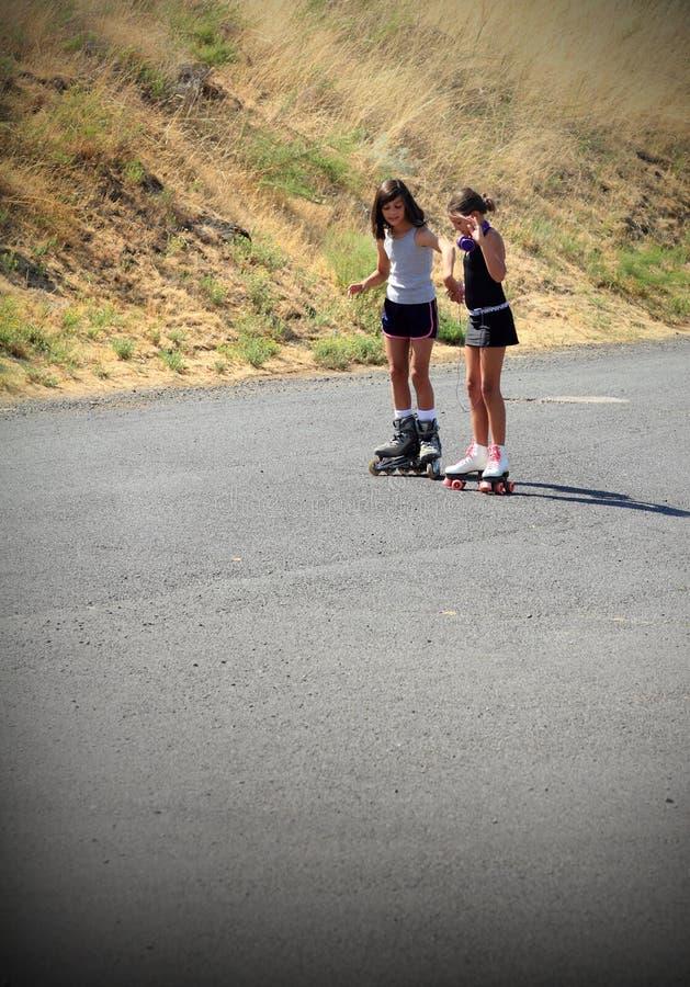 Girl Teaching Friend to Roller Skate royalty free stock photo