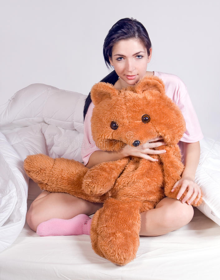 Girl with teddy bear in bed stock photography