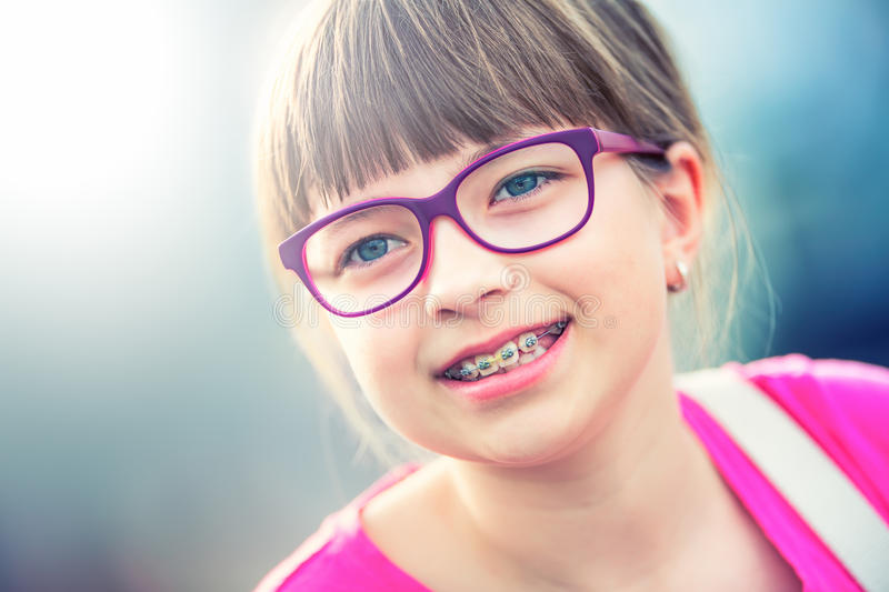 Girl. Teen. Pre teen. Girl with glasses. Girl with teeth braces. Young cute caucasian blond girl wearing teeth braces and glasses stock images