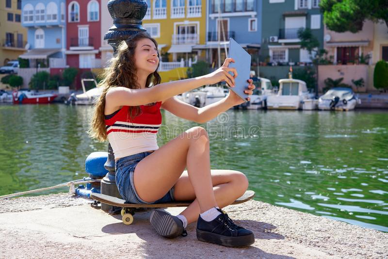 Girl teen with skateboard and tablet selfie. Playing with touch on marina stock images