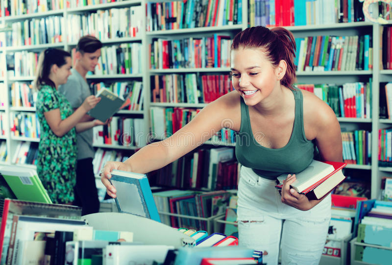Girl teenager choosing book in shop royalty free stock photos