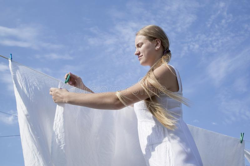 Girl teenager with clothespins fixing white sheets them on clothesline. Drying clean laundry on outdoors stock photography