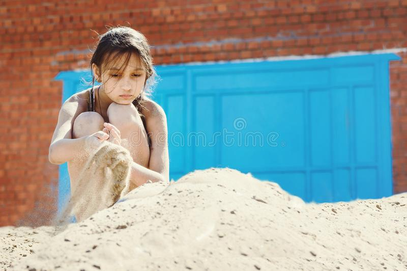 Girl teenager digging into the sand on the beach after swimming in the river on a summer sunny day stock photo