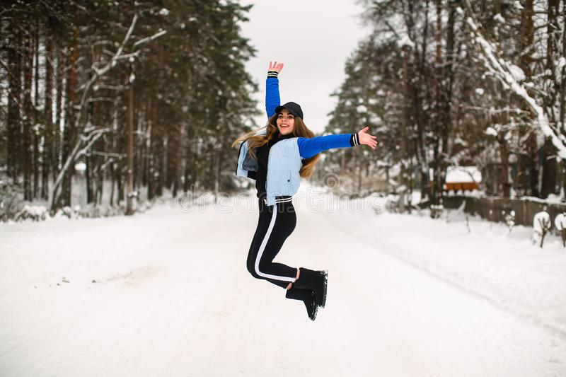 Girl teenager fun jumping outdoors in snowly winter. Girl teenager jumping outdoors in snowly winter stock photo