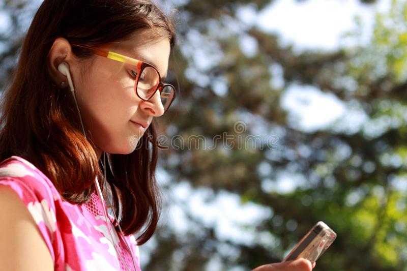 Girl teenager in glasses listening to music from a mobile phone. Portrait of a girl in headphones close-up. royalty free stock photos