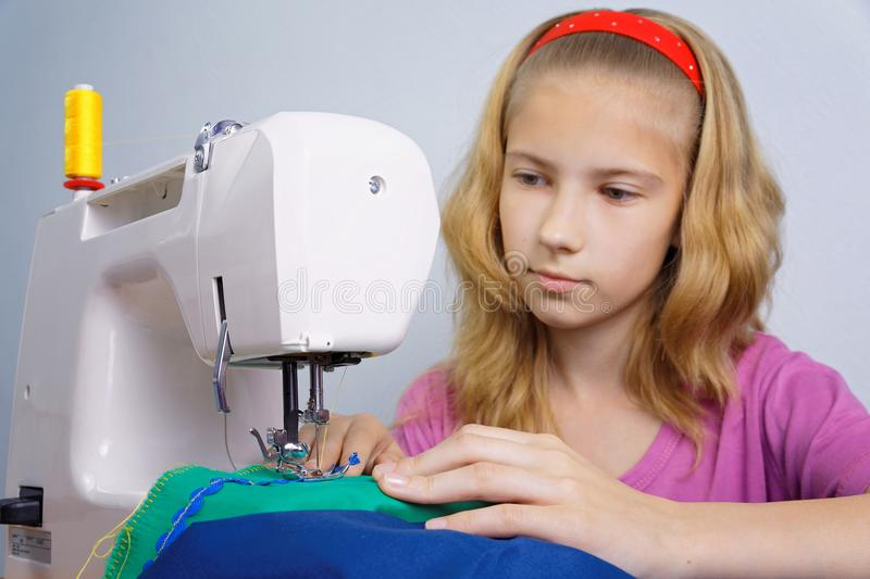 Girl learns to sew on an electric sewing machine. Girl teenager happy to sew on the sewing machine. Focus on her hands and a sewing needle with thread royalty free stock photo