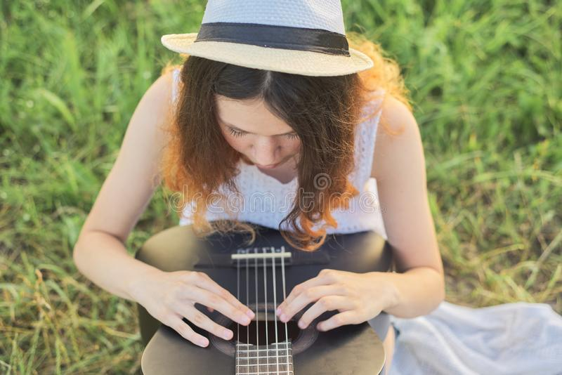 Girl teenager in hat playing guitar sitting on the grass stock photography