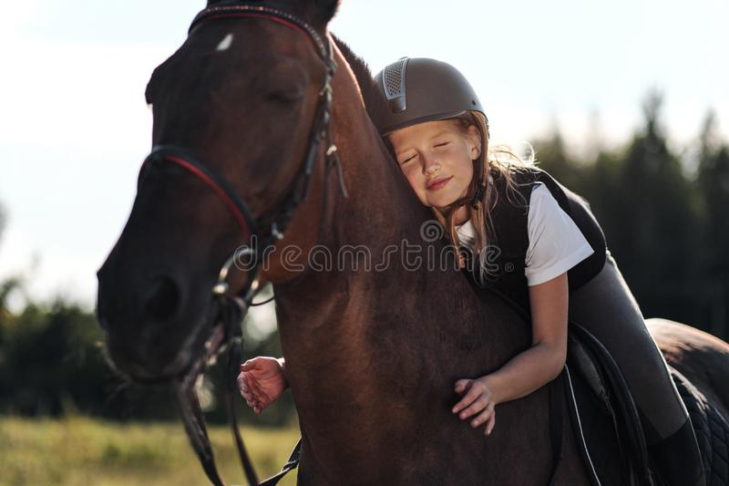 Girl teenager jockey sits on a brown horse, hugs and strokes her. Rider`s love of a horse royalty free stock photos