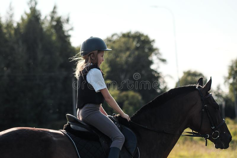 Girl teenager jockey trains on the field and at the hippodrome. Gallop and trot royalty free stock photography