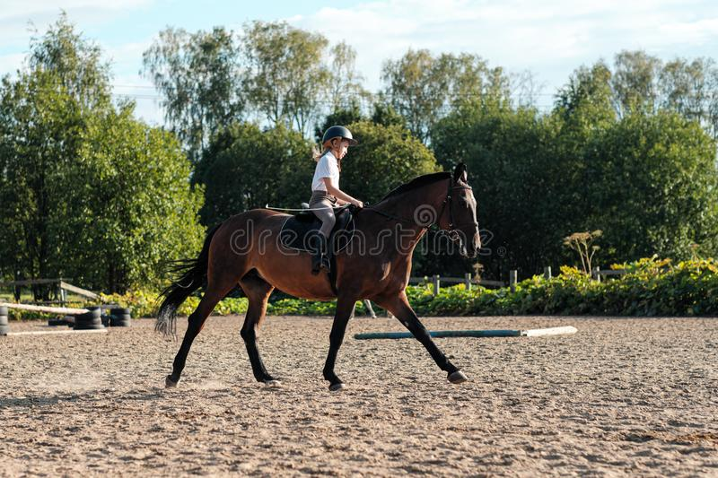 Girl teenager jockey trains on the field and at the hippodrome. Gallop and trot stock photo