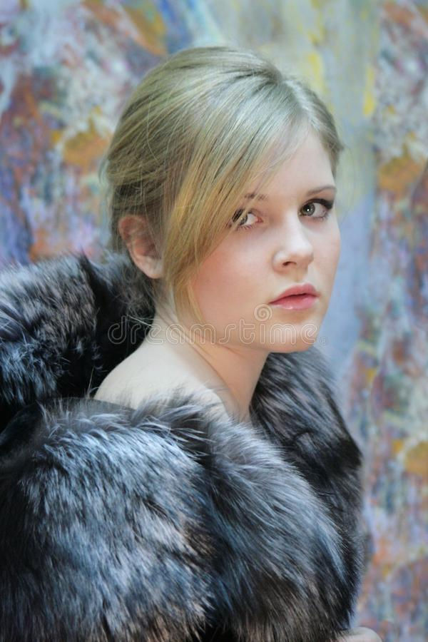 Girl - teenager, natural blonde in a chic fur coat from silver fox stock images