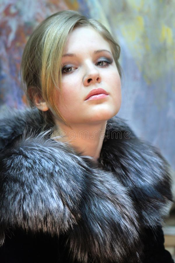 Girl - teenager, natural blonde in a chic fur coat from silver fox stock photography