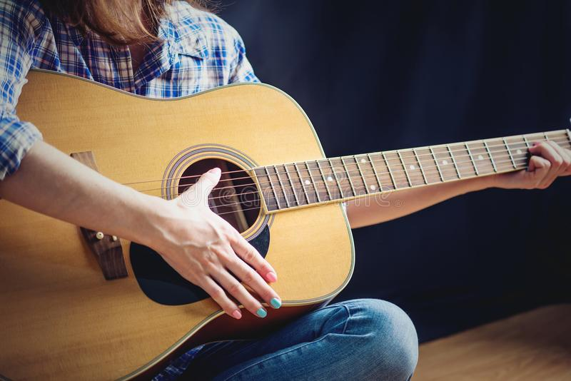 Girl teenager playing an acoustic guitar on a dark background in the Studio. Concert young musicians royalty free stock images