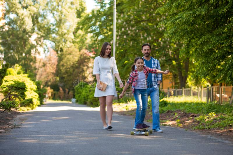 Girl Teenager Is Riding A Skateboard In The City Park. Parents Watching Her. stock photo