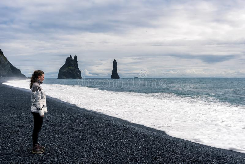 Girl teenager sating in the Reynisfjara black sand beach in Southern Iceland.  Reynisdrangar basalt sea stacks are at background. Girl teenager sating in the royalty free stock photo