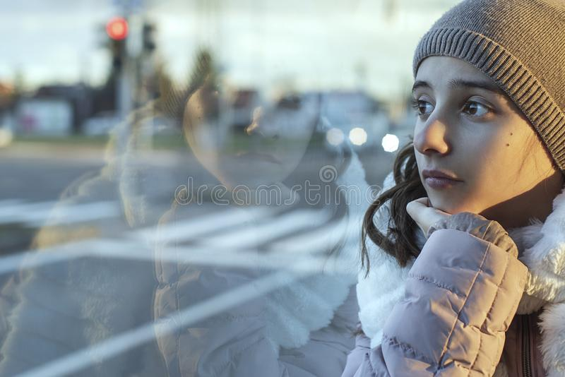 Girl teenager sits on the bus and looks out the window,teenager girl is sitting in the bus looking forward thinking. royalty free stock photography