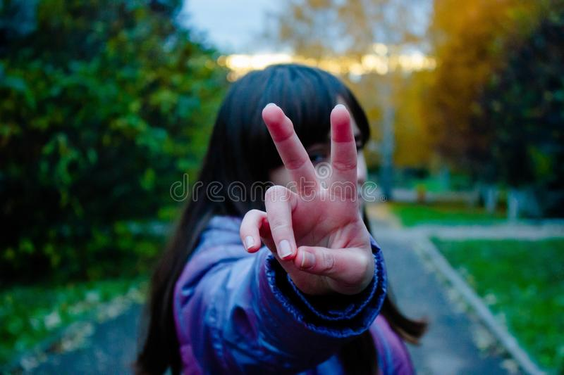 teenager girl who shows a gesture of victory. Symbol V, symbol of peace stock image