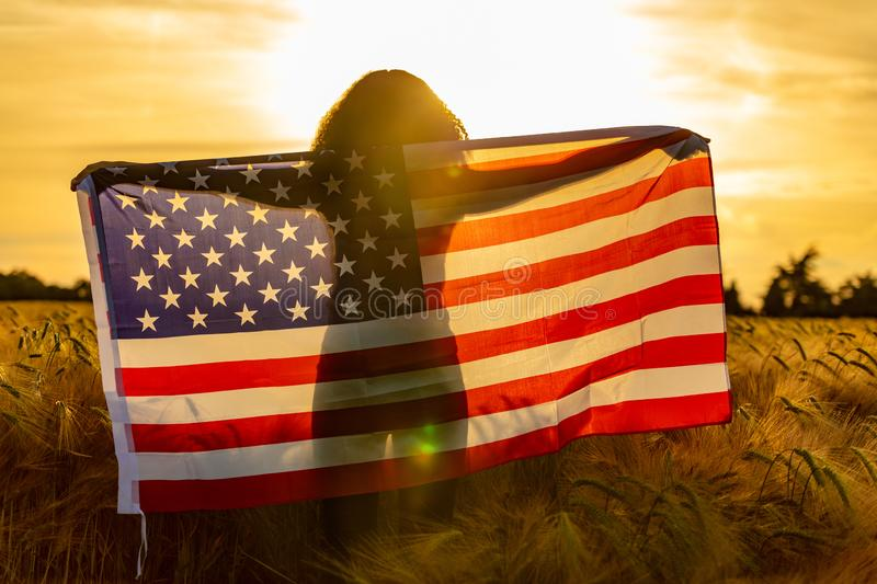 Girl Teenager Wrapped in USA Flag in Field at Sunset. Mixed race African American girl teenager female young woman in a field of wheat or barley crops wrapped in royalty free stock images