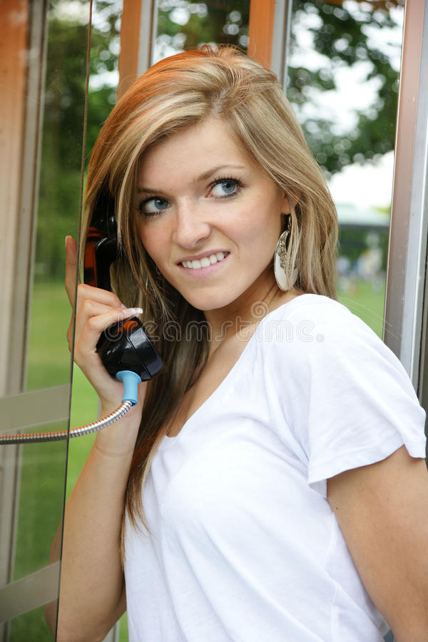 Girl in the telephone booth royalty free stock photo