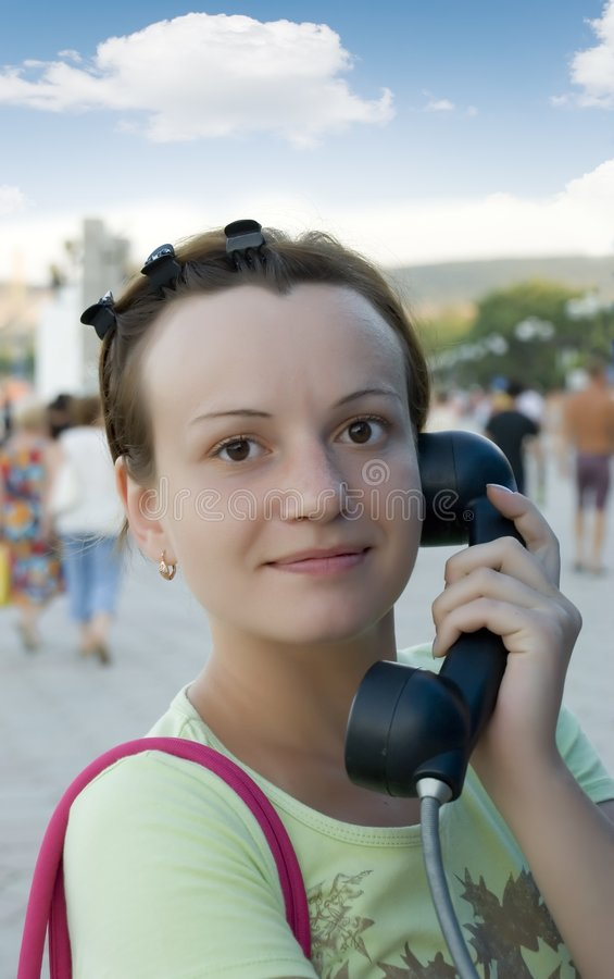 The girl with a telephone tube. The girl speaking on a call box in the street royalty free stock photography