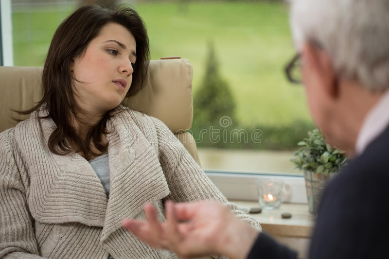 Girl telling about her troubles. During psychotherapy session stock photography