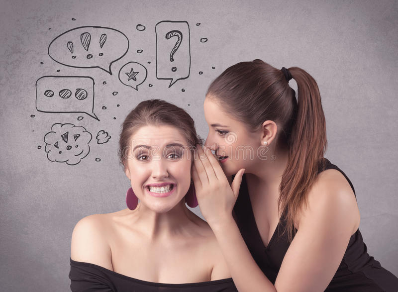 Girl telling secret things to her girlfriend. Two girls chatting and sharing their secrets concept with drawn chat bubbles on the background urban wall stock photos