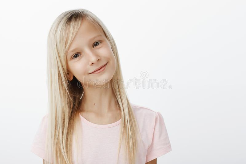 Girl tells mom she likes boy from class. Portrait of pleased positive cute kid with happy satisfied smile, tilting head royalty free stock photos