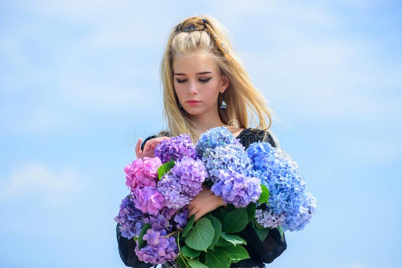 Girl tender blonde hold hydrangea bouquet. Skin care and beauty treatment. Springtime bloom. Gentle flowers for delicate. Woman. Tenderness of young skin. Pure royalty free stock photos