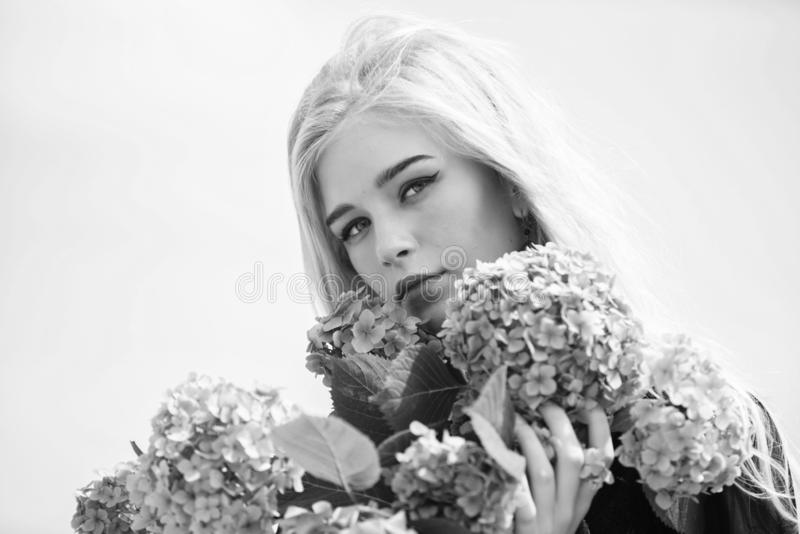 Girl tender blonde hold hydrangea flowers bouquet. Springtime bloom. Natural beauty concept. Skin care and beauty. Treatment. Gentle flower for delicate woman stock image