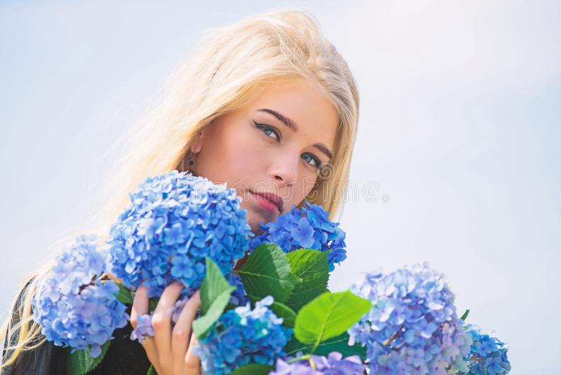 Girl tender blonde hold hydrangea flowers bouquet. Springtime bloom. Natural beauty concept. Skin care and beauty. Treatment. Gentle flower for delicate woman stock images