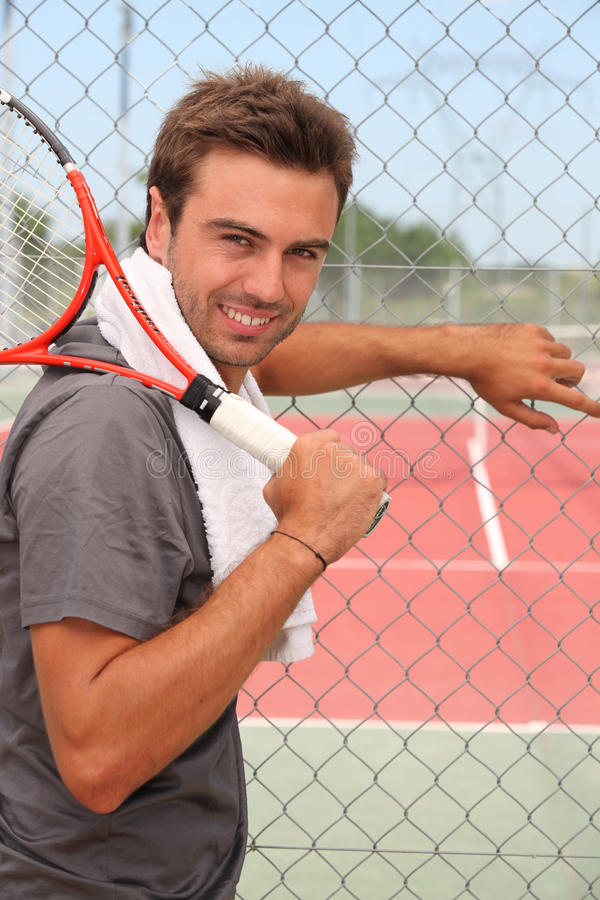 Girl with tennis racket. Girl holding a tennis racket nex to the court stock photos