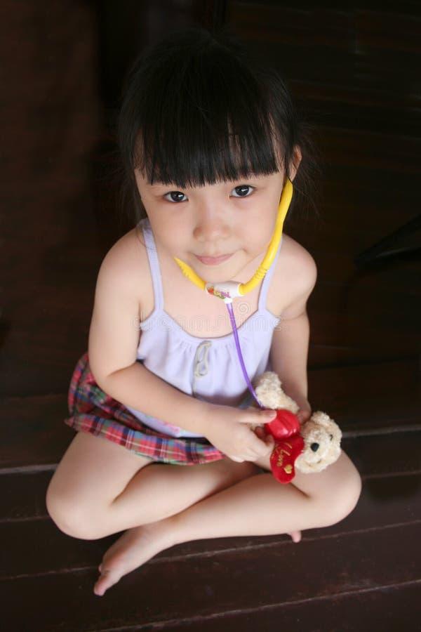 Girl testing stethoscope on toy dog stock image