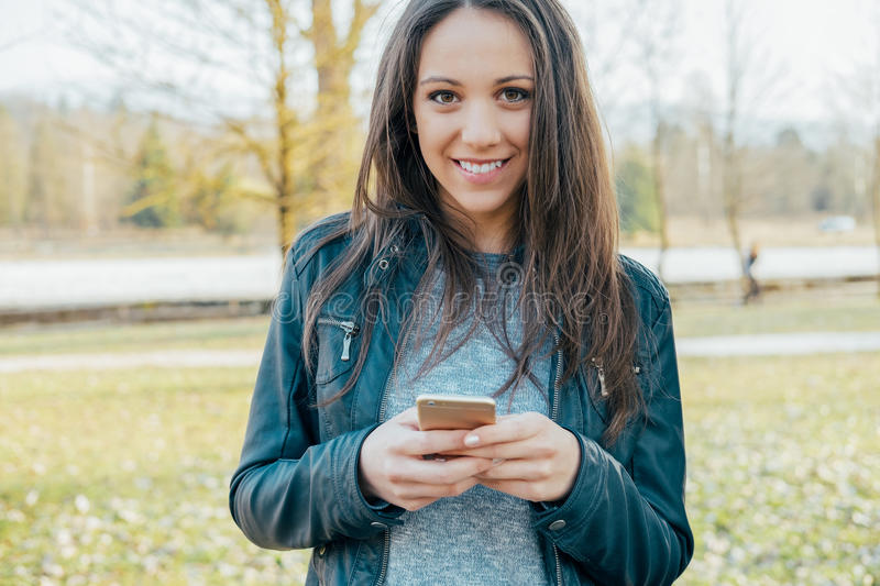Girl texting with her phone royalty free stock photography
