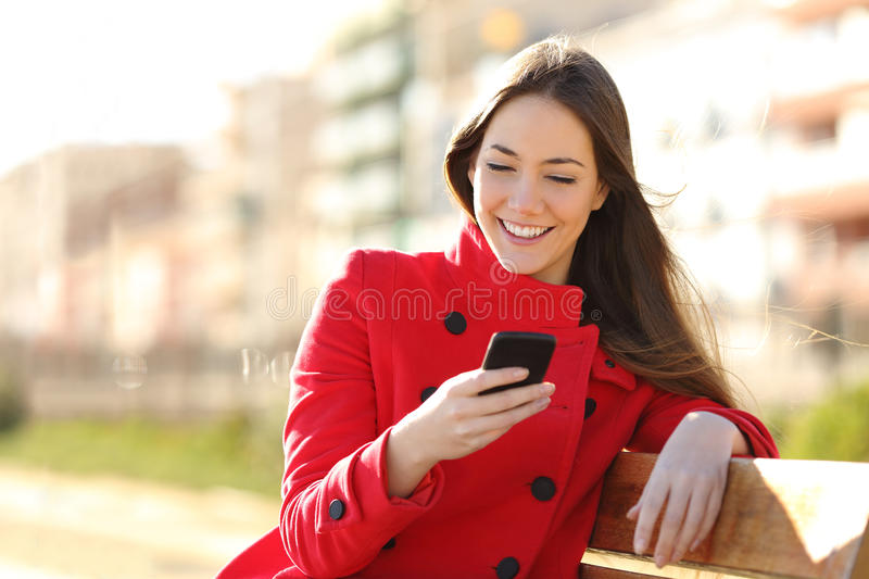 Girl texting on the smart phone sitting in a park. Wearing a red jacket and sitting in a bench in a park