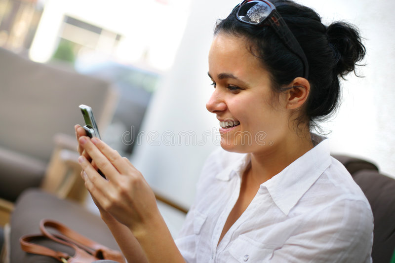 Girl texting sms. Young woman reading sms message on cell phone royalty free stock image