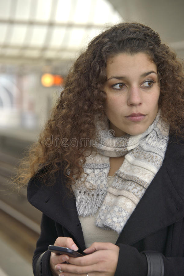 Girl texting in train station royalty free stock images