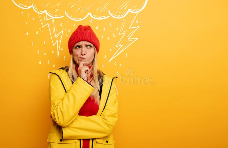Girl thinks about negative things. Cloud, rain and lightning above her. Confused and pensive expression. Yellow. Blonde Girl thinks about negative things. Cloud royalty free stock photography
